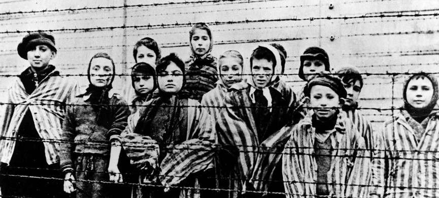 FILE — A picture taken just after the liberation by the Soviet army in January, 1945, shows a group of children wearing concentration camp uniforms behind barbed wire fencing in the Auschwitz Nazi concentration camp. One of the black-uniformed men on the ramp where people arrived was likely SS guard Oskar Groening who goes on trial Tuesday, April 21, 2015 in a state court in the northern city of Lueneburg on 300,000 counts of accessory to murder. (AP Photo/FILE)