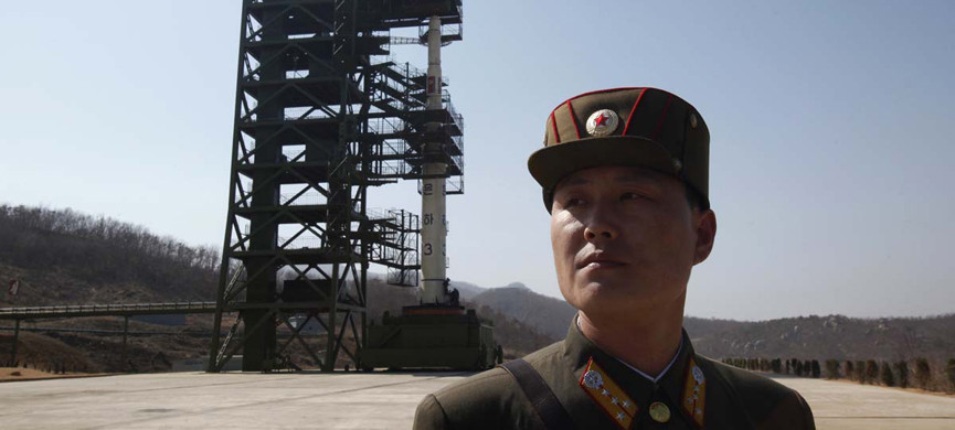A soldier stands guard in front of the Unha-3 (Milky Way 3) rocket sitting on a launch pad at the West Sea Satellite Launch Site, during a guided media tour by North Korean authorities in the northwest of Pyongyang April 8, 2012. North Korea has readied a rocket for a launch from a forested valley in its remote northwest this week that will showcase the reclusive state's ability to fire a missile with the capacity to hit the continental United States. Picture taken April 8, 2012. REUTERS/Bobby Yip (NORTH KOREA — Tags: POLITICS MILITARY) ORG XMIT: PYG17
