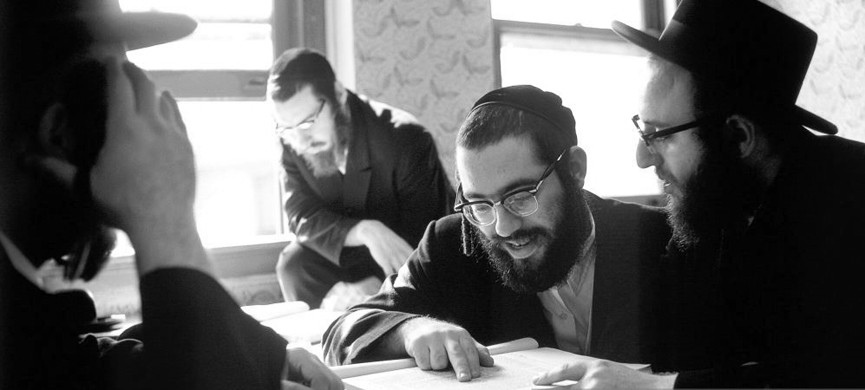 BROOKLYN, NY � OCTOBER 25, 1972: Hasidic Jewish men studying books of Talmud and Jewish law in yeshiva in Williamsburg, Brooklyn, New York on October 25, 1972. The students are wearing beards, yarmulkes, glasses, and hair sidelocks (side locks) (peyes). The men are being trained to be rabbis at the Satmer Yeshiva school of rabbinical studies. The students are mostly from the religious and observant Satmer Hasidim community in Williamsburg, Brooklyn. The classes are held in English and Yiddish language, and the books are in Hebrew. (Photo by Nathan Benn/Corbis via Getty Images)