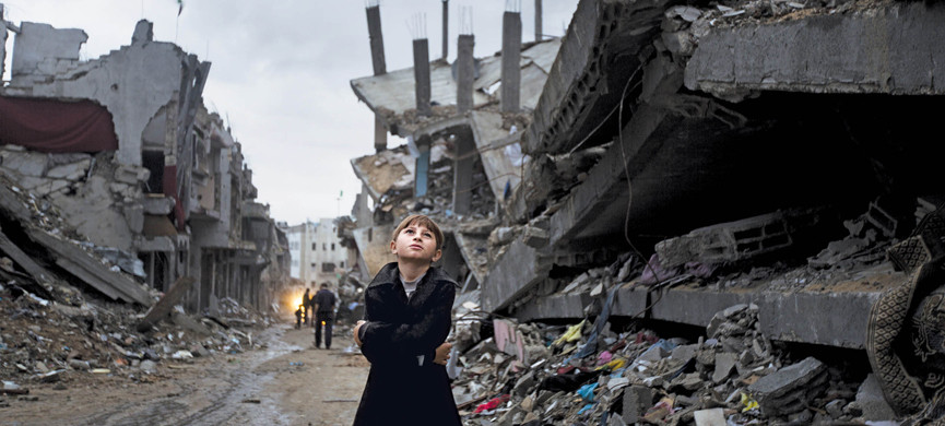 A Palestinian boy looks up during a rain storm while walking through a neighbourhood destroyed during the 50 day conflict between Israel and Hamas, in the Shejaiya neighbourhood of Gaza City on October 19, 2014. United Nations chief Ban Ki-moon said that the promised aid funds to rebuild would go towards the