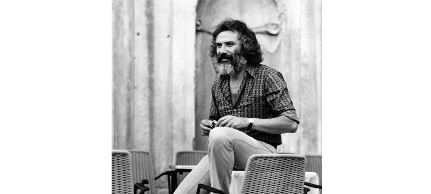 Французский композитор, певец и гитарист греческого происхождения Жорж Мустаки (Giuseppe Mustacchi) сидит на столе. Венеция, 1970-е (Фото Рино Петросино / Портфолио Мондадори через Getty Images)