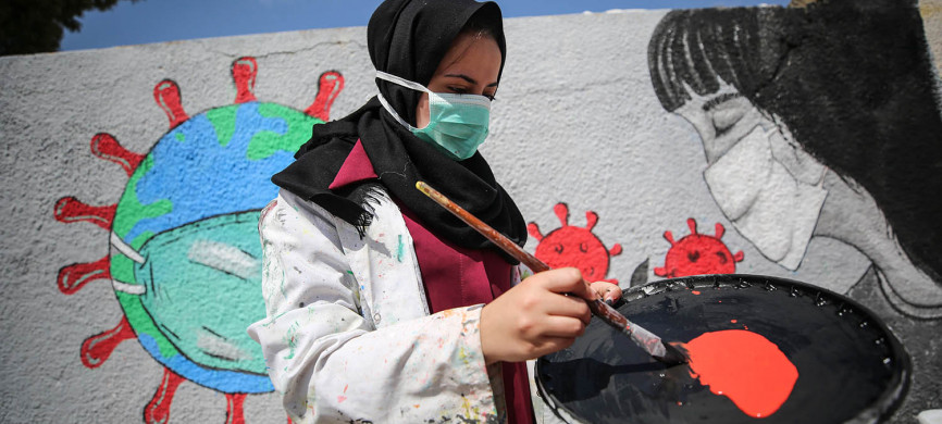 <p>Palestinian painters work on a mural to draw attention to the novel coronavirus pandemic in Khan Yunis, Gaza, on March 28. Mustafa Hassona/Anadolu Agency via Getty Images</p>