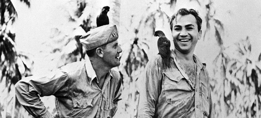 "<p>(Original Caption) 3/13/1943-Guadalcanal-Corporal Barney Ross of the United Staes Marine Corps is shown in this photo with Father Frederick Gehring,Catholic Chaplain on Guadalcanal,as they made friends with two ""Peace Birds""who alighted on them on Island of ""Kill or be Killed."" Ross has paid a remarkable tribute to Father Gehring,who is a former teacher at St. John's Prep School in Brooklyn.Over his heart Ross wears a little Catholic medal next to his own Jewish Mezuzeh. The medal was given him by Father Gehring.</p>"